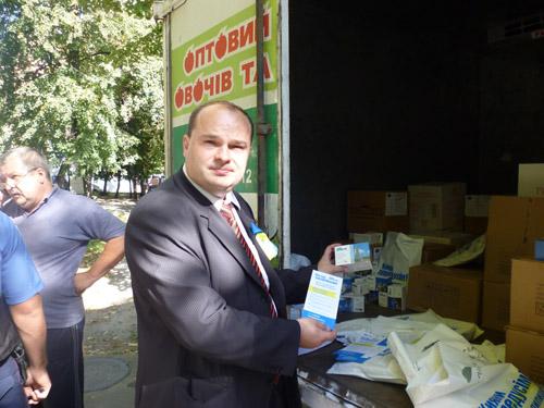 На фото кандидат В. Гладчук демонстрирует пакеты с чаем с фамилией Пилипишин